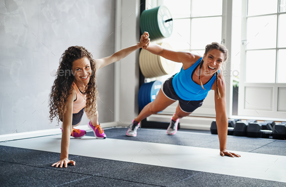 Smiling friends high fiving each other while exercising together - Stock Photo - Images
