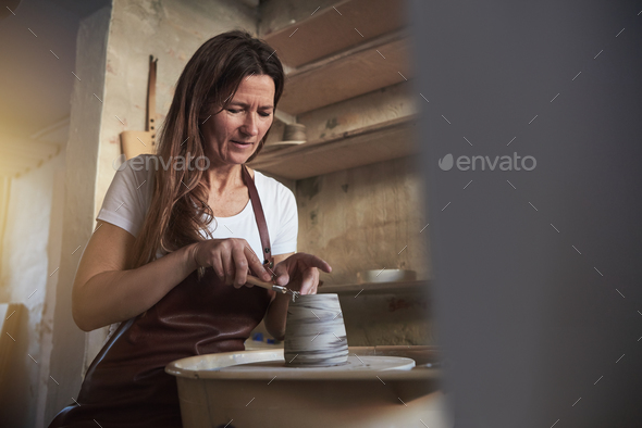 Female artisan getting creative in her pottery studio - Stock Photo - Images