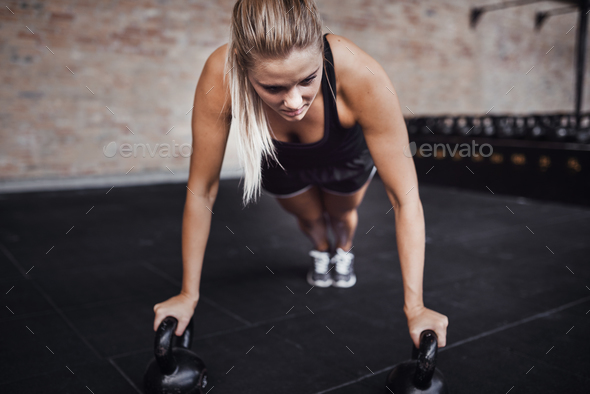 Focused young woman doing pushups with weights in a gym - Stock Photo - Images