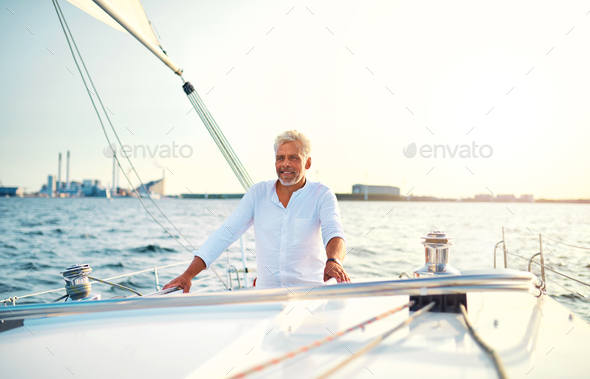 Mature man standing on the deck of his sailboat - Stock Photo - Images