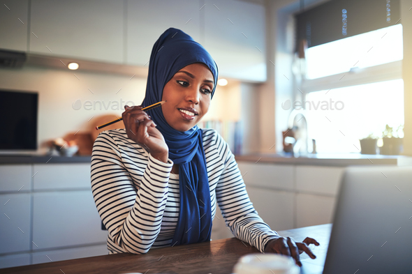 Smiling Arabic female entrepreneur working online in her kitchen - Stock Photo - Images