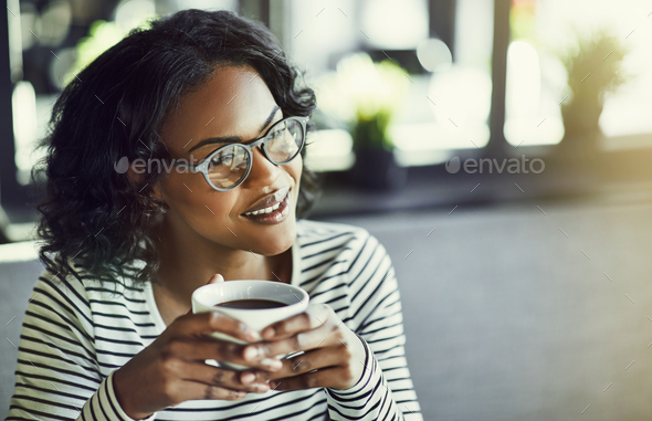 Young African woman sitting in a cafe enjoying some coffee - Stock Photo - Images
