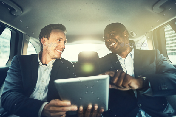 Business colleagues working online in the backseat of a car - Stock Photo - Images