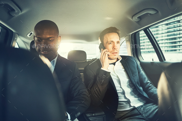 Two Businessmen working in the backseat of a car - Stock Photo - Images