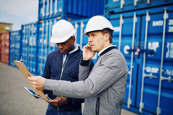 Engineers working in a large commercial freight shipping yard - Stock Photo - Images