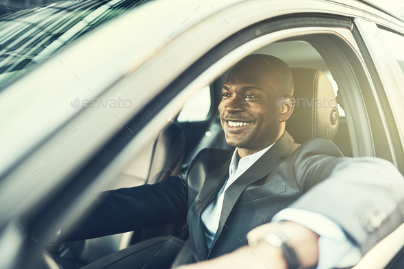 African businessman smiling while driving his car in the city - Stock Photo - Images