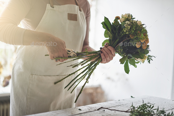 Female florist trimming flowers while working in her shop - Stock Photo - Images