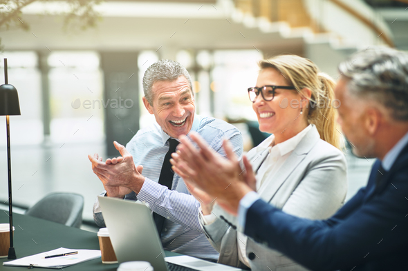 Mature office colleagues smiling and clapping together after a presentation - Stock Photo - Images