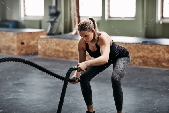 Young woman working out with ropes at the gym - Stock Photo - Images