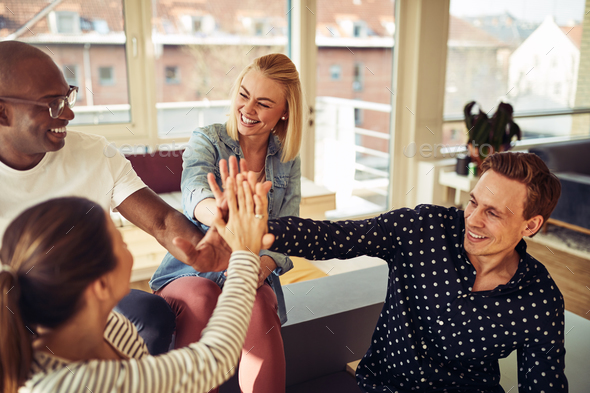 Diverse business colleagues high fiving together in an office - Stock Photo - Images