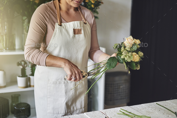 Female florist working in her flower shop trimming a bouquet - Stock Photo - Images