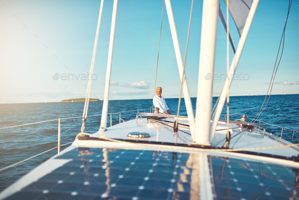 Smiling mature man standing on the deck of his sailboat - Stock Photo - Images