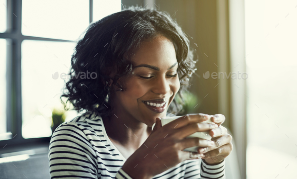 Smiling young African woman enjoying a fresh cup of coffee - Stock Photo - Images
