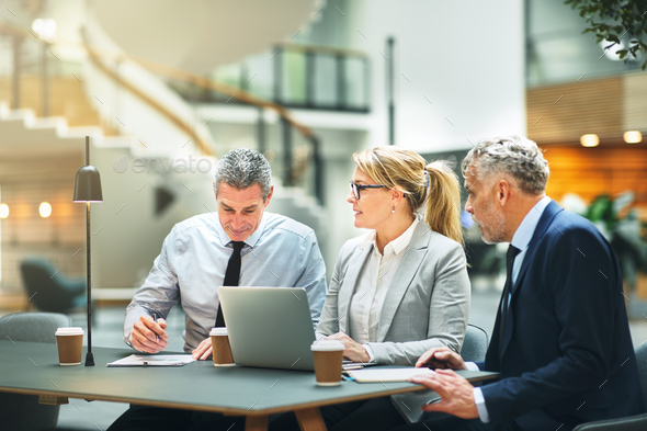 Mature work colleagues talking business together in an office - Stock Photo - Images