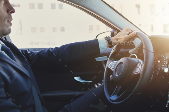 Stylish businessman holding steering wheel and driving - Stock Photo - Images