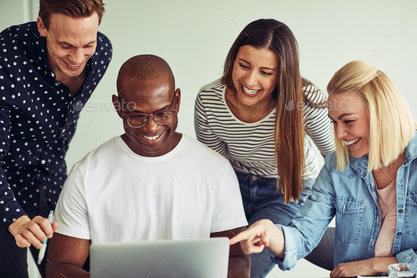Smiling group of diverse businesspeople working on a laptop together - Stock Photo - Images