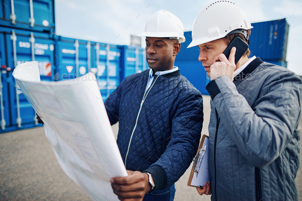 Engineers standing in a freight yard discussing building plans - Stock Photo - Images