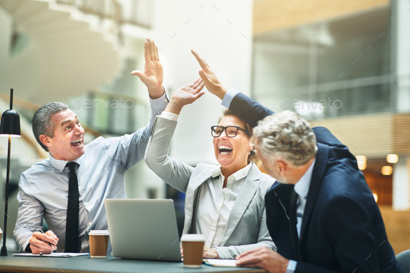 Mature businesspeople excitedly high fiving together in an office - Stock Photo - Images