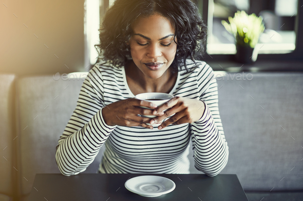 Young African woman enjoying a fresh cup of coffee - Stock Photo - Images