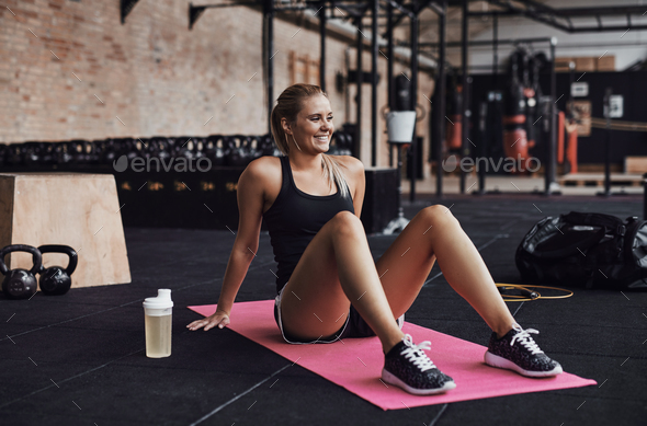 Smiling woman sitting on a gym floor after working out - Stock Photo - Images