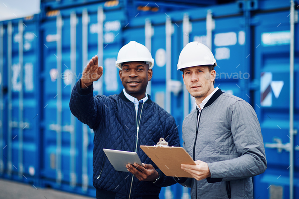 Smiling engineers tracking freight containers in a large shipping yard - Stock Photo - Images