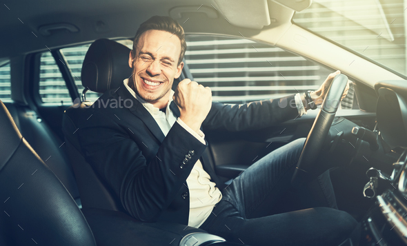 Ecstatic businessman fist pumping while driving in the city - Stock Photo - Images