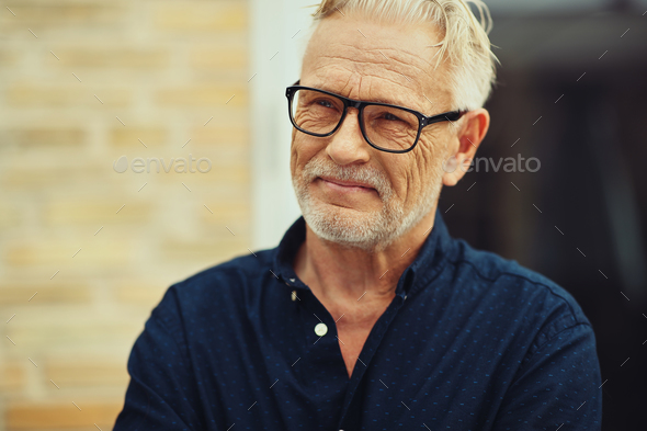 Smiling senior man standing outside in his yard - Stock Photo - Images