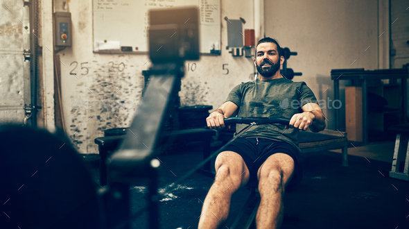 Fit young man working out on a gym rowing machine - Stock Photo - Images