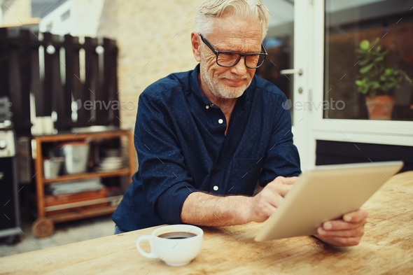 Smiling senior man drinking coffee and using a digital tablet - Stock Photo - Images