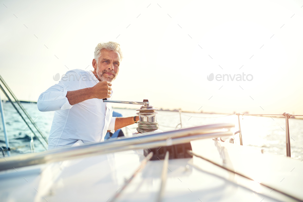 Mature man winding a winch on his sailboat - Stock Photo - Images