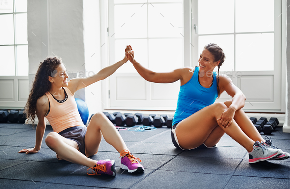 Two smiling female friends high fiving together at the gym - Stock Photo - Images
