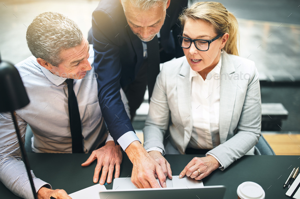Manager discussing business with two colleagues on a laptop - Stock Photo - Images