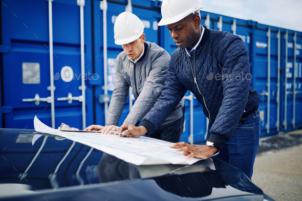 Two engineers discussing building plans together in a freight yard - Stock Photo - Images