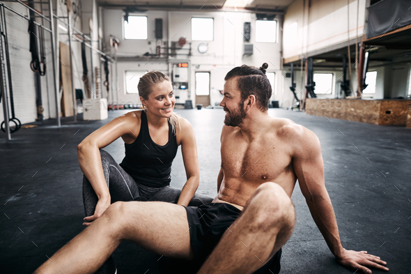 Fit people resting on a gym floor after working out - Stock Photo - Images