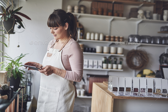 Florist working with a digital tablet in her flower shop - Stock Photo - Images