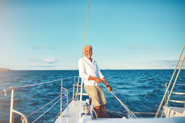 Smiling mature man out for a sail on his boat - Stock Photo - Images