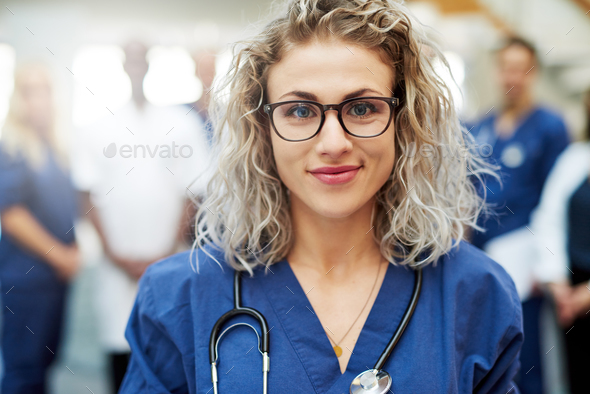 Pretty medic in hospital looking at camera - Stock Photo - Images