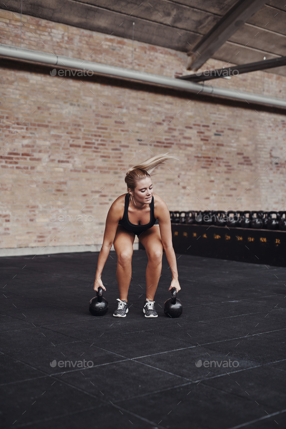 Young woman exercising with weights alone in a gym - Stock Photo - Images