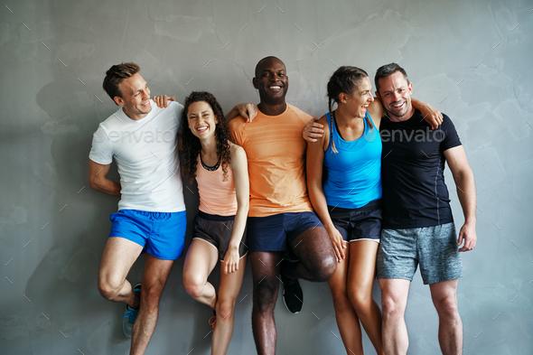 Diverse friends in sportswear laughing together in a gym - Stock Photo - Images