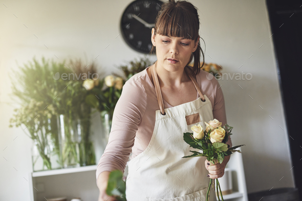 Young female florist making a bouquet in her flower shop - Stock Photo - Images