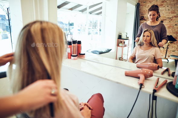 Woman looking in a salon mirror talking with her hairstylist - Stock Photo - Images