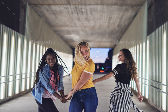 Diverse young female friends walking through the city at night - Stock Photo - Images