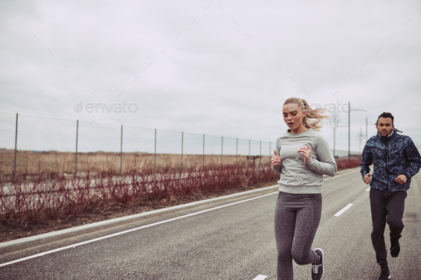 Diverse young couple in sportswear jogging along a country road - Stock Photo - Images