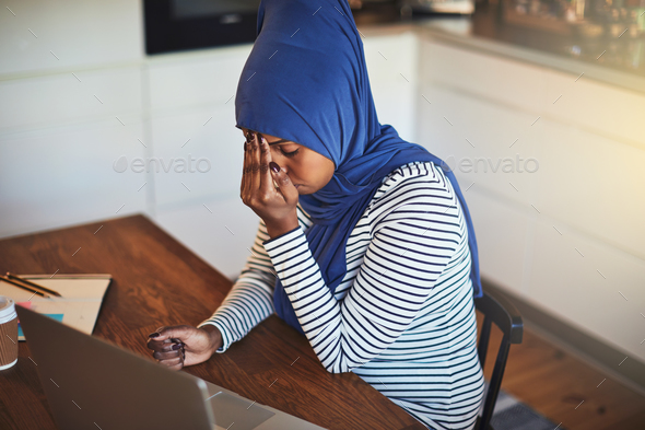 Young Arabic female entrepreneur sitting at home looking stressed out - Stock Photo - Images