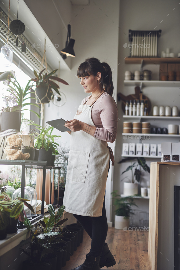 Female florist standing in her flower shop using a tablet - Stock Photo - Images