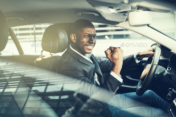 Smiling African businessman fist pumping while driving in his car - Stock Photo - Images