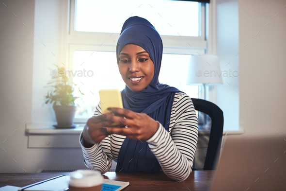 Smiling Arabic woman sitting at home sending a text message - Stock Photo - Images