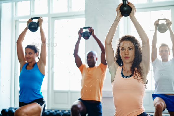 Focused group of people lifting weights together at a gym - Stock Photo - Images