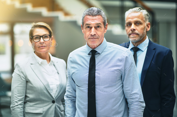 Confident mature businessman standing with colleagues in an office - Stock Photo - Images