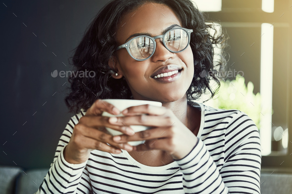 Smiling young African woman enjoying coffee in a cafe - Stock Photo - Images
